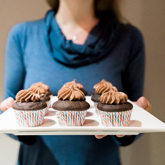 Amelie hold tray of Chocolate Cupcakes.